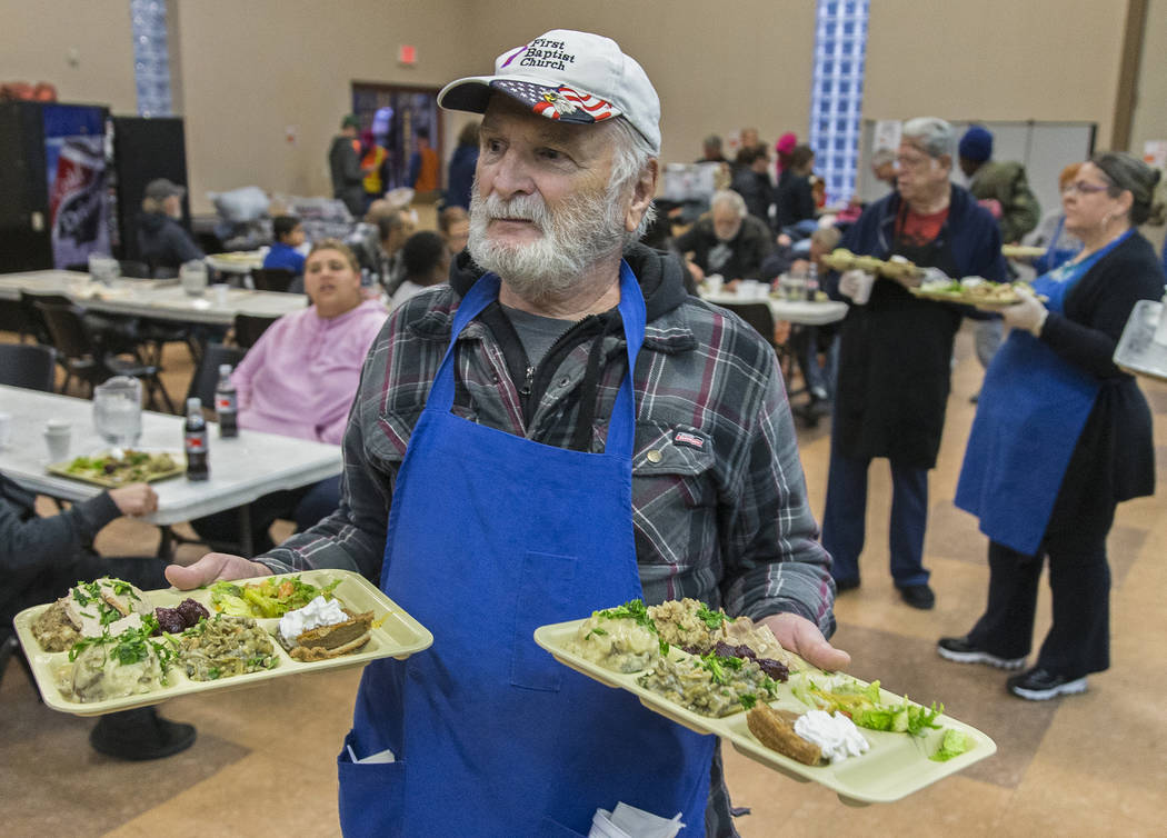 Volunteer Earl Thomas serves trays of food during the Las Vegas Rescue Mission's annual Thanksg ...