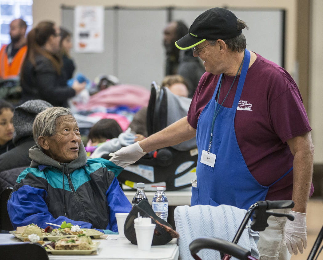 Volunteer Eric Marsh, right, talks with Yeng Huang while Huang eats at the Las Vegas Rescue Mis ...