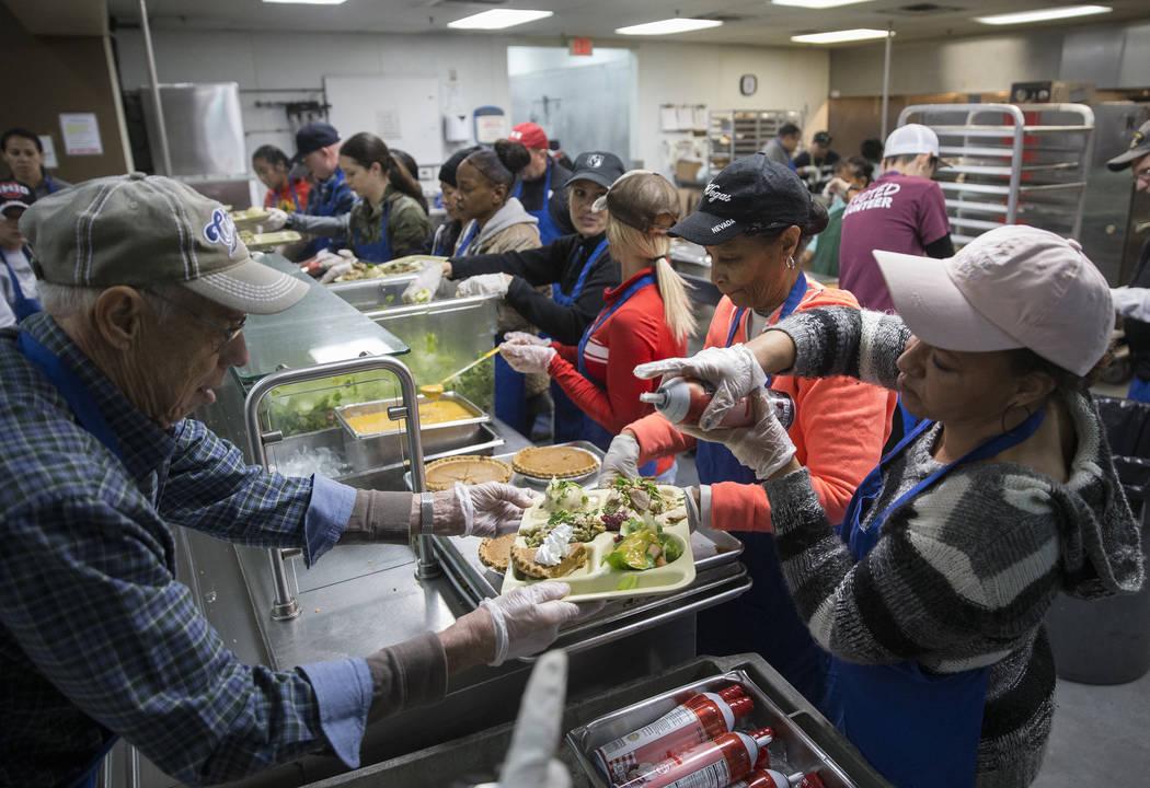 Edna Sanders, top/right, Sara Cottingham and Joe Kubacki prepare trays of food during the Las V ...