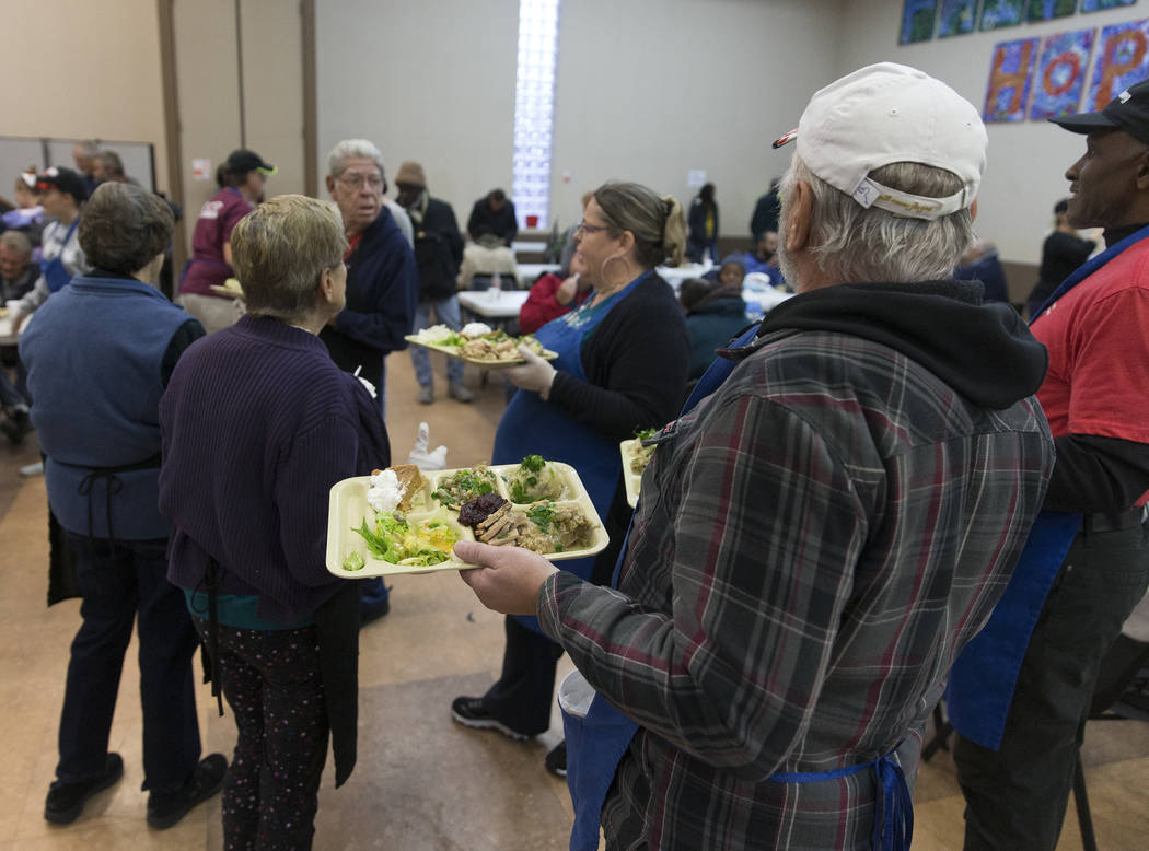 Volunteer Earl Thomas, bottom/right, serves trays of food during the Las Vegas Rescue Mission's ...