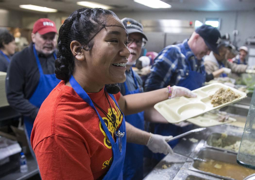 Volunteer Britany Bautista prepares trays of food during the Las Vegas Rescue Mission's annual ...