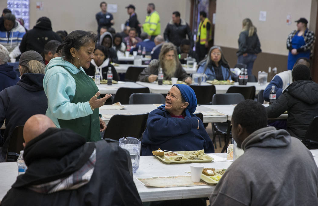 Volunteer Barbara Callahan, top/left, talks with attendees during the Las Vegas Rescue Mission' ...