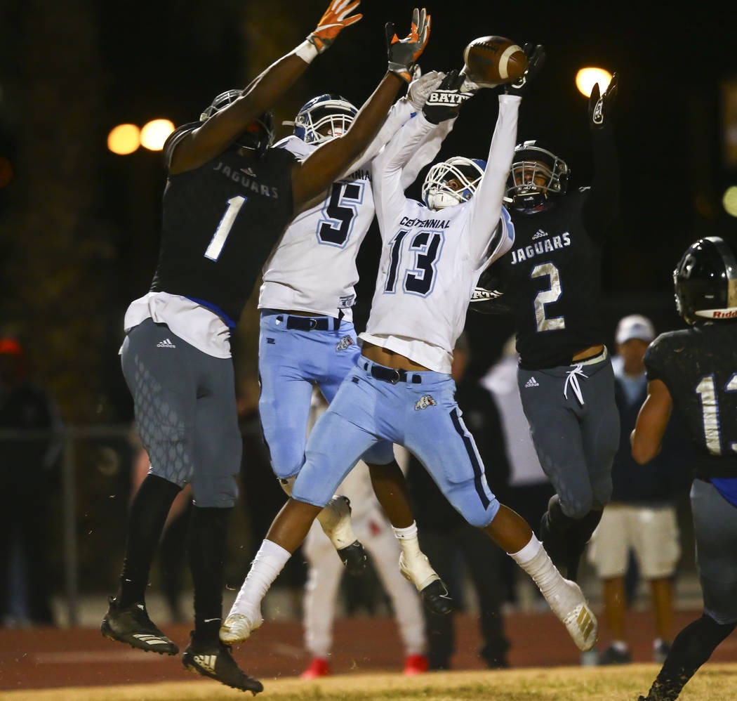 Centennial's Tyrone McCoy (5) and Ronaven Mokiao (13) break up a pass in front of Desert Pines' ...