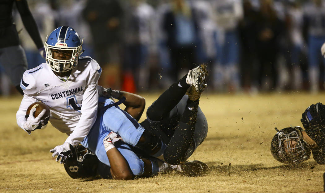 Centennial's Jordan Smith (1) gets stopped by Desert Pines' Will Paden (8) during the second ha ...