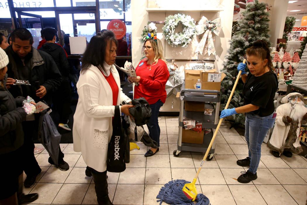Imelda Alvarez keeps the floor dry as General Manager Renee Lanctot hands out early Black Frida ...