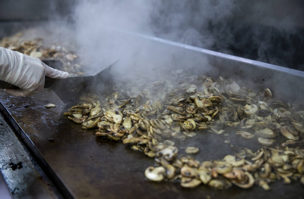 Steam rises from a grill full of mushrooms being prepared as Catholic Charities of Southern Nev ...