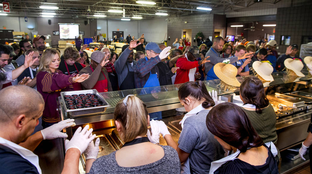 Volunteers come together for a group prayer over the food as Catholic Charities of Southern Nev ...