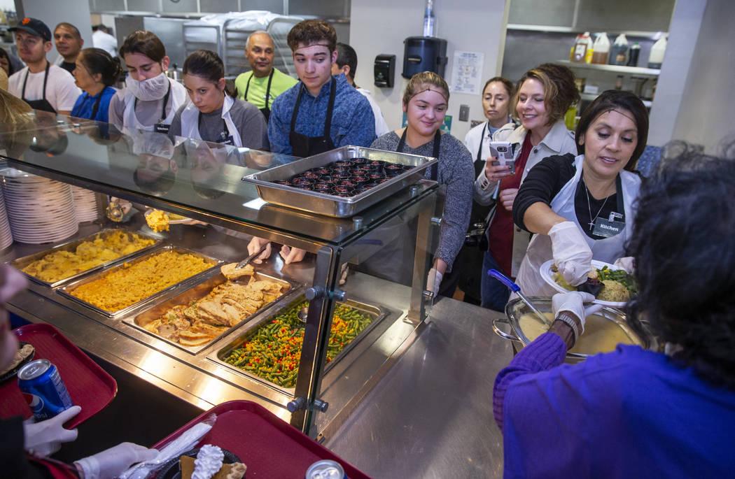 Volunteers begin to prepare plates of food as Catholic Charities of Southern Nevada serves its ...