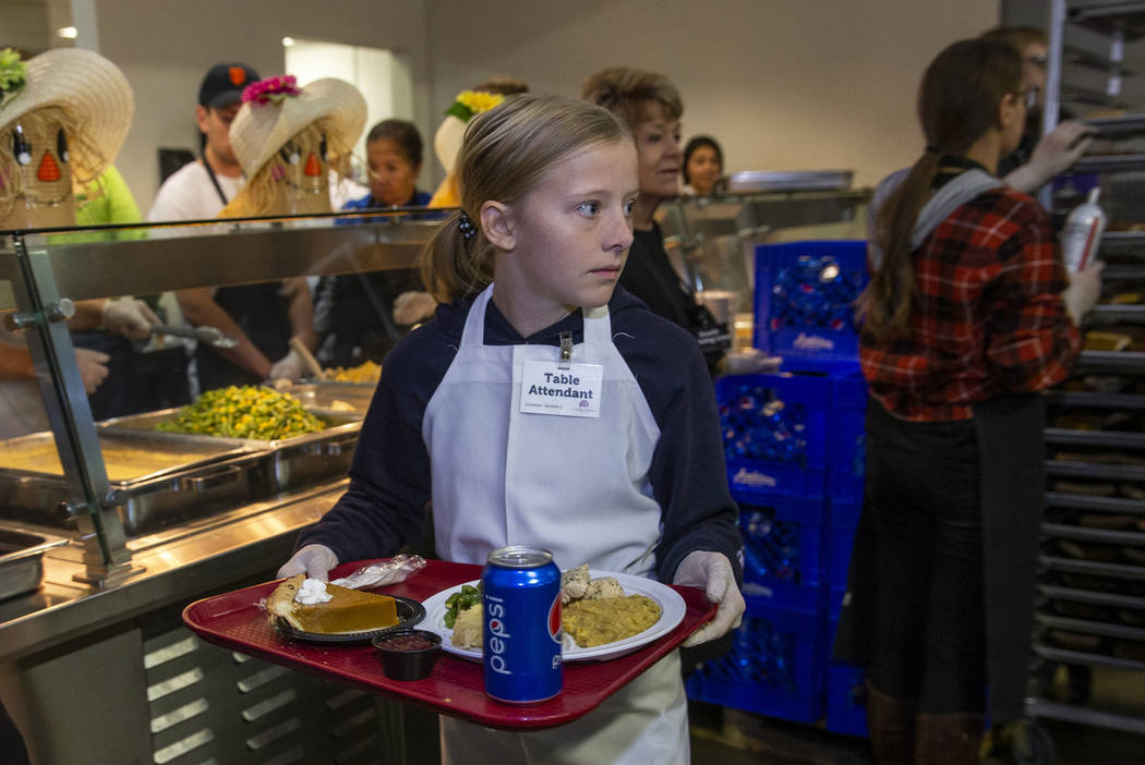 Volunteers Evyn Pallett, 12, carries over another full tray as Catholic Charities of Southern N ...