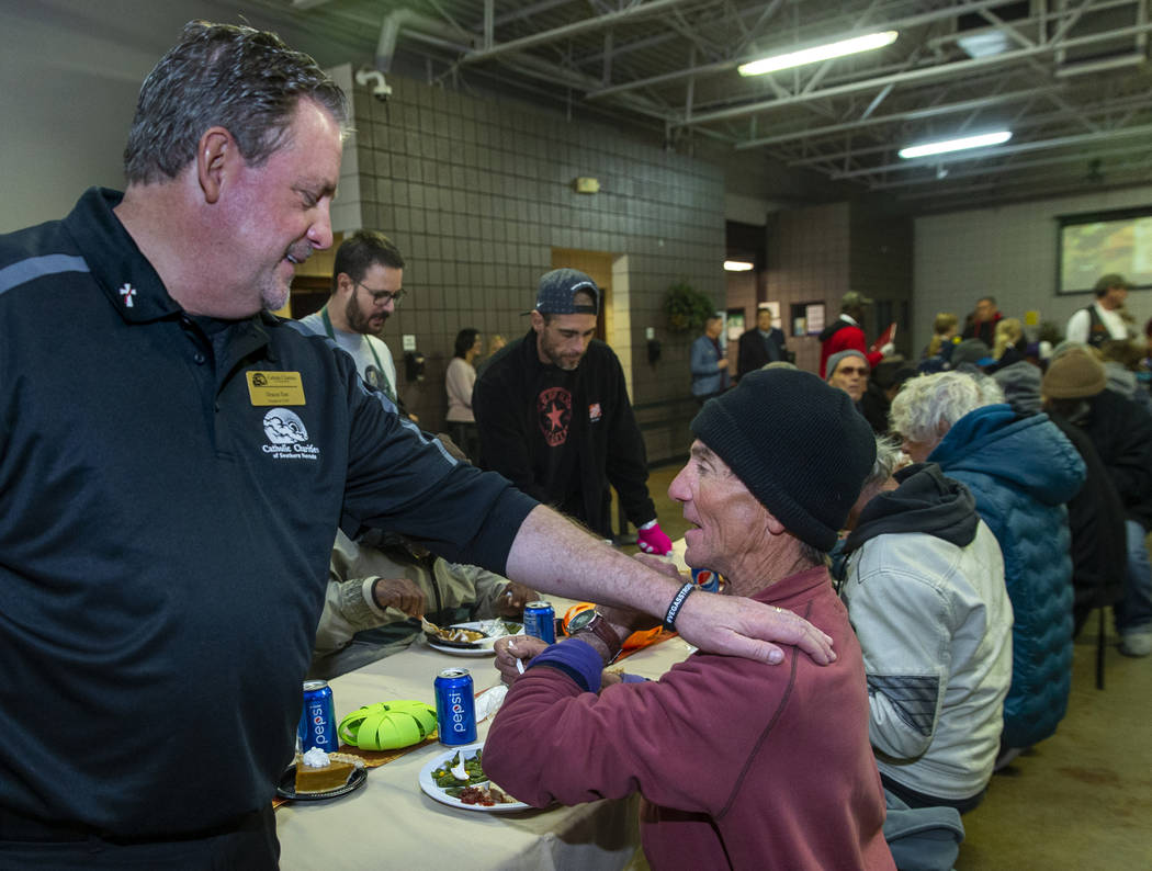 Deacon Tom Roberts, president and CEO of Catholic Charities of Southern Nevada, talks with dine ...