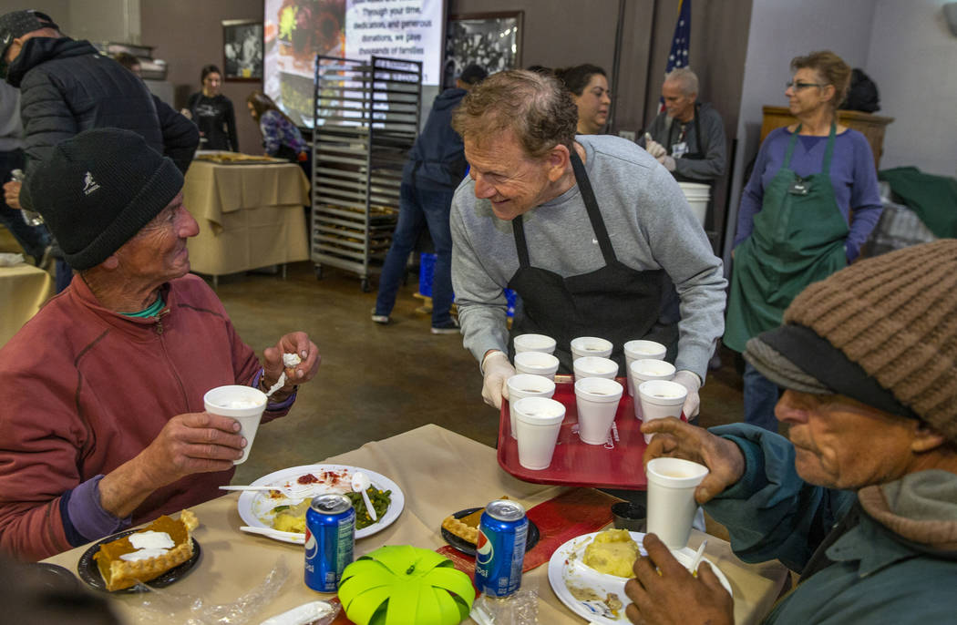 Fred Berkley, center, delivers hot chocolate to diner Jeff Ward, left, and others as Catholic C ...
