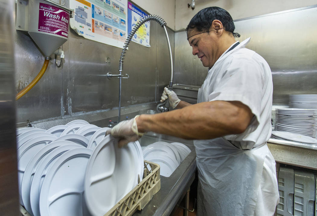 Jun Lata works to help clean the dishes as Catholic Charities of Southern Nevada serves its 54t ...