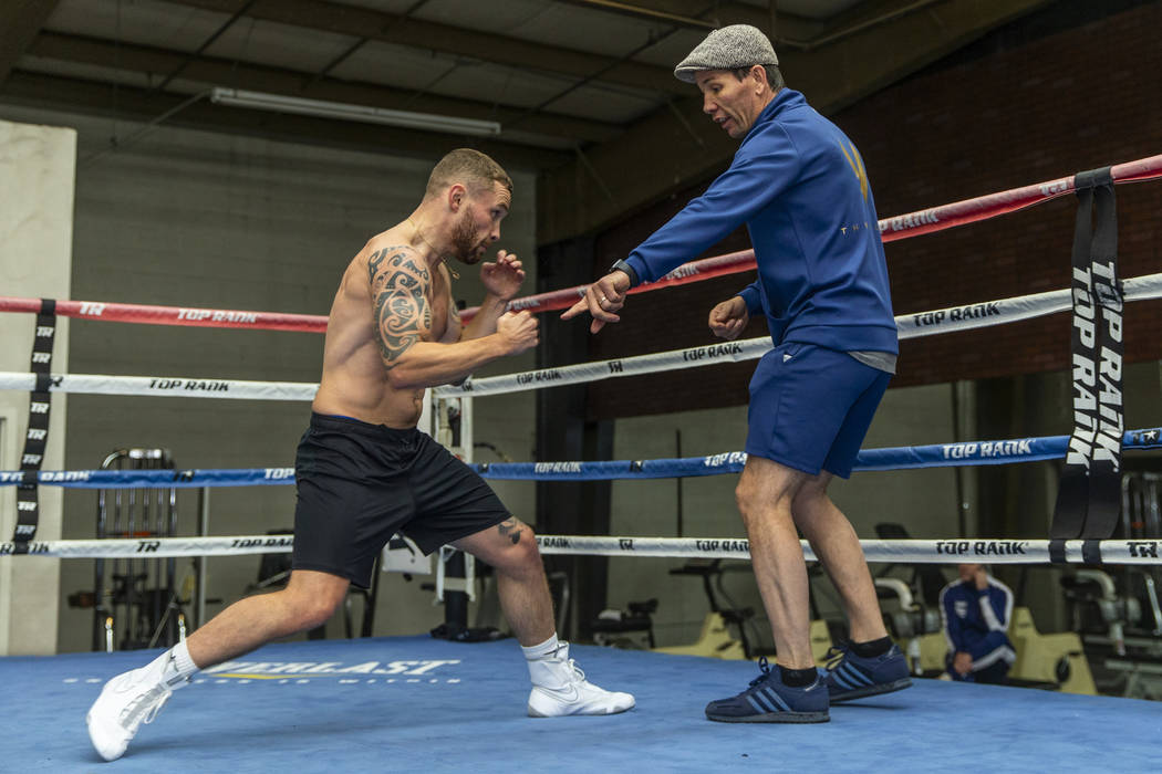 Former two-weight world boxing champion Carl Frampton, left, works on his footing with trainer ...