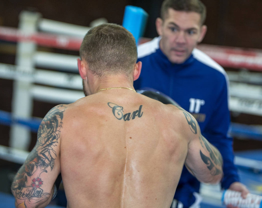 Former two-weight world boxing champion Carl Frampton boxes with trainer Jamie Moore, facing, a ...