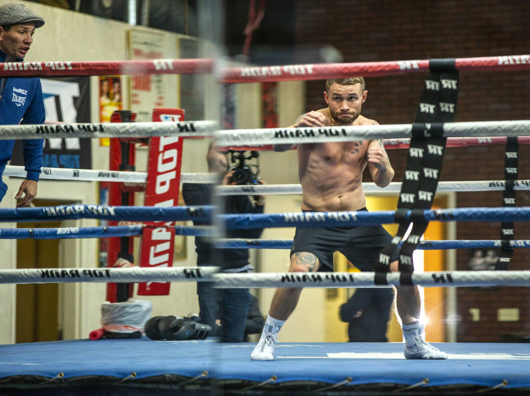 Former two-weight world boxing champion Carl Frampton, center, shadow boxes in the ring with tr ...