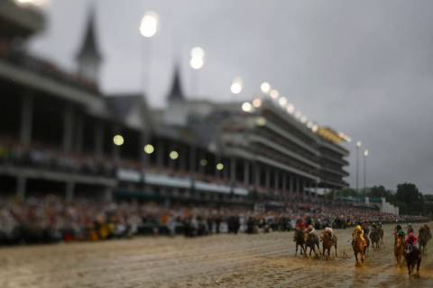 In this photo made with a tilt shift lens, Luis Saez rides Maximum Security across the finish l ...