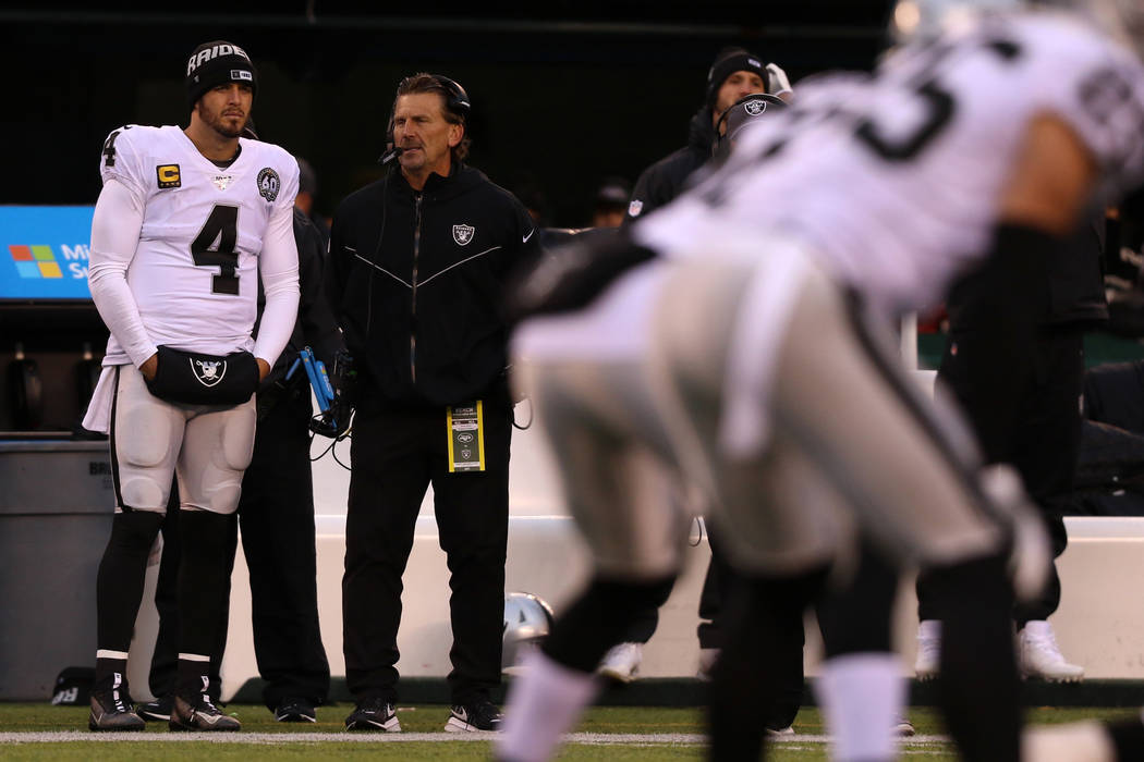 Oakland Raiders quarterback Derek Carr (4) watches from the sideline with offensive coordinator ...