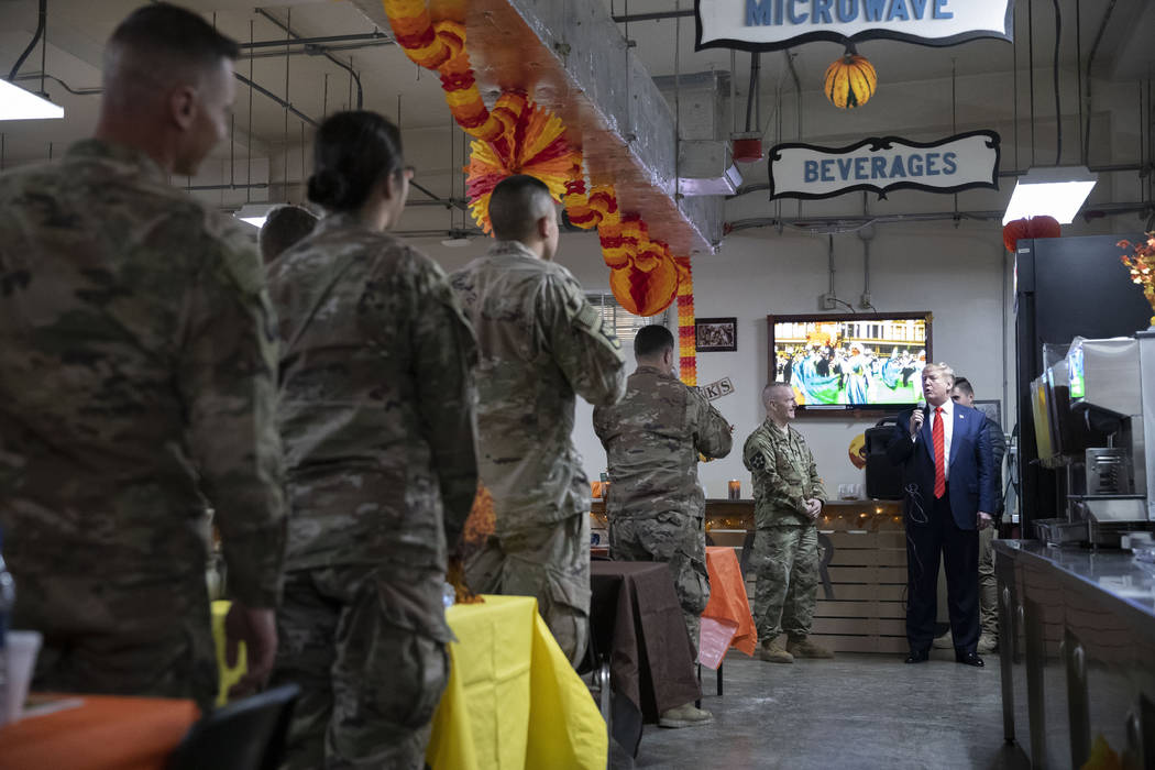 President Donald Trump speaks during a surprise Thanksgiving Day visit to the troops, Thursday, ...