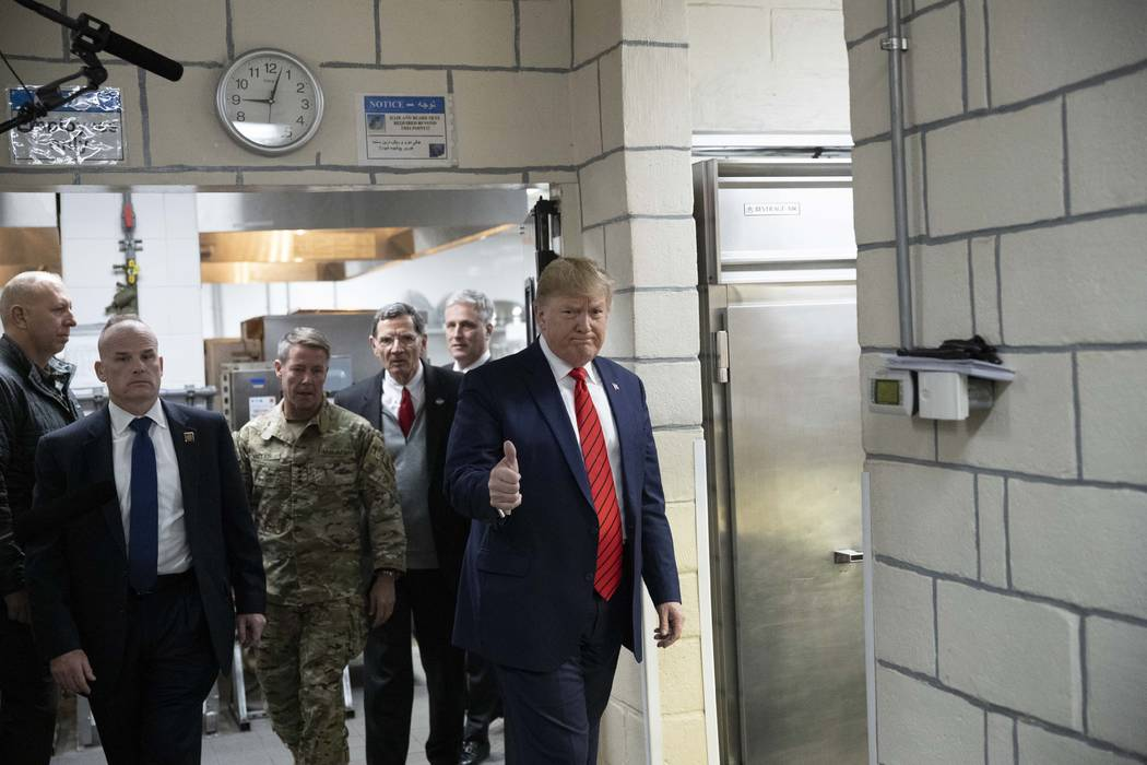 President Donald Trump gives thumbs up as he walks to serve dinner during a surprise Thanksgivi ...