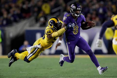 Baltimore Ravens quarterback Lamar Jackson, right, is tackled by Los Angeles Rams defensive end ...