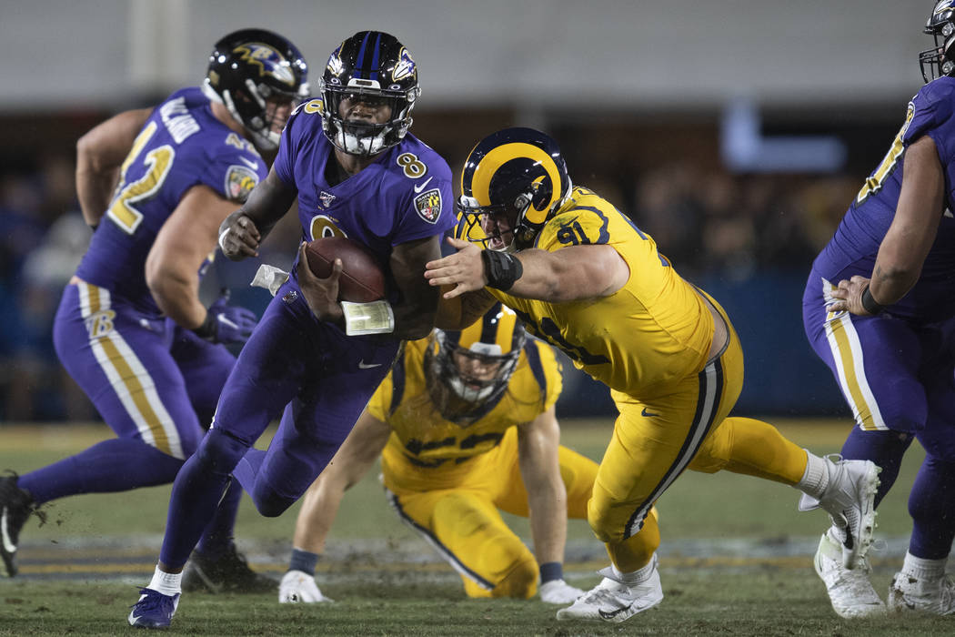 Baltimore Ravens quarterback Lamar Jackson, second from left, sprints with the ball past Los An ...