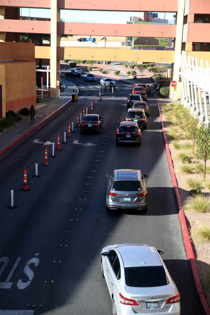 Cars file into a parking garage at Las Vegas North Premium Outlets before opening on Thanksgivi ...