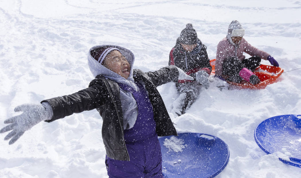 Matthew Pham, 4, of Las Vegas, left, throws snow into the air while sledding with his brother M ...