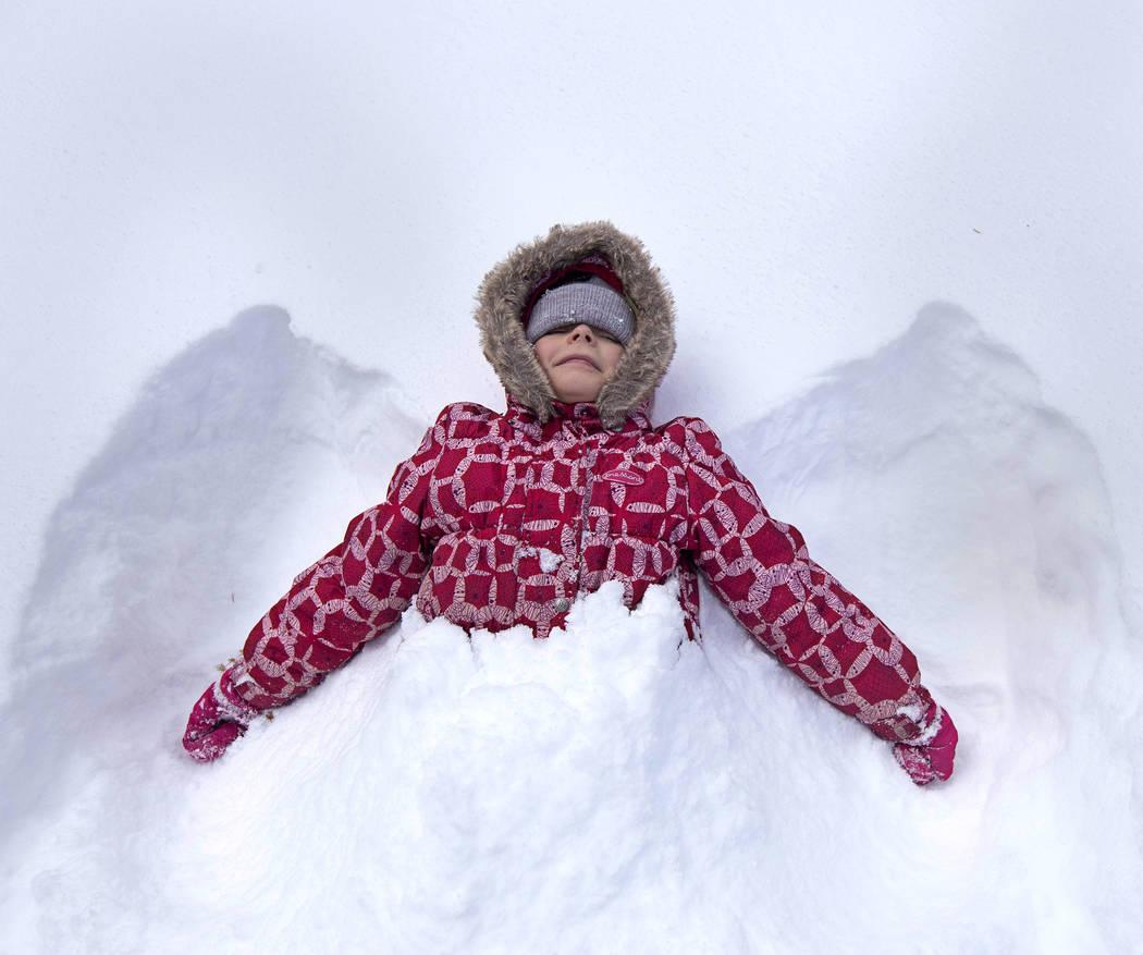 Maria Kutanova, 8, of Las Vegas makes a snow angel on Thursday, Nov. 28, 2019, at Upper Lee Mea ...
