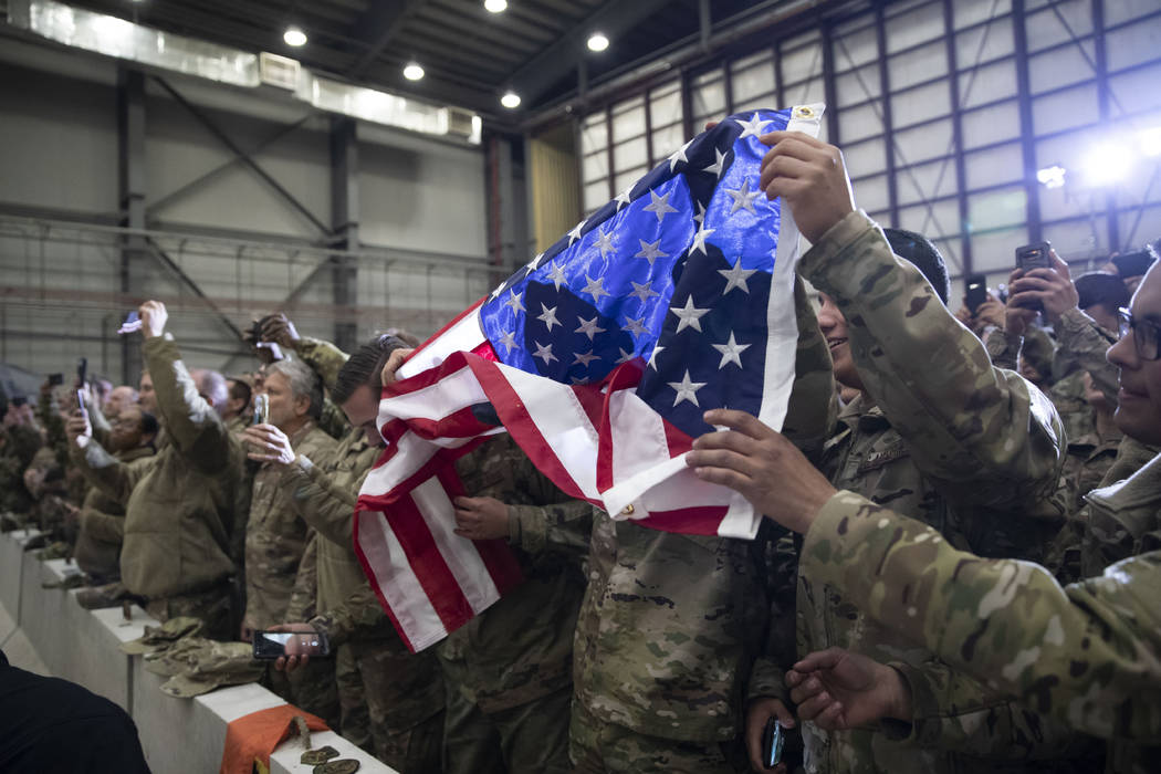 Members of the military unfurl an American flag as President Donald Trump speaks during a surpr ...