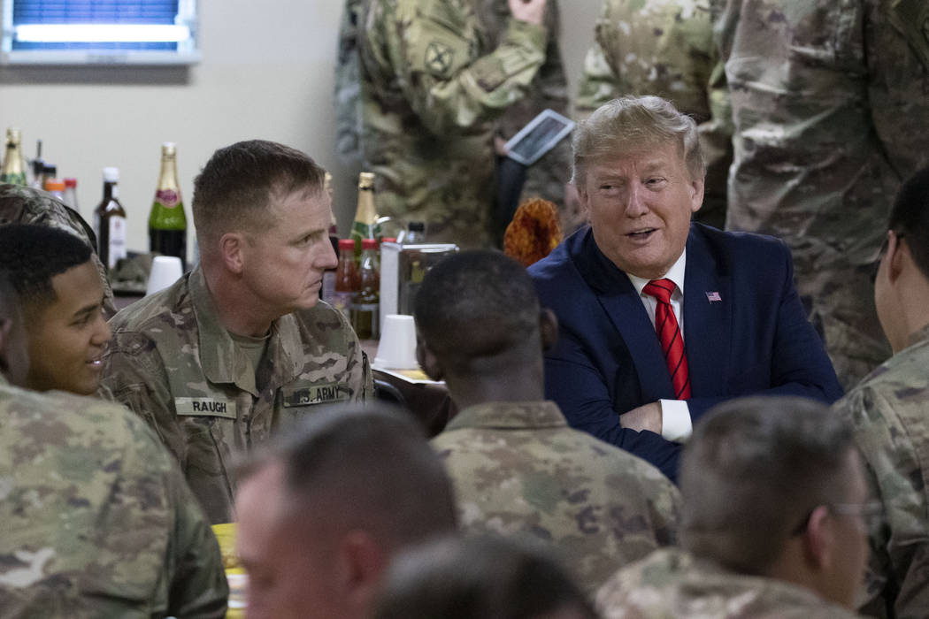 President Donald Trump speaks with members of the military during a surprise Thanksgiving Day v ...