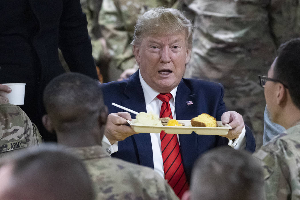 President Donald Trump holds up a tray of Thanksgiving dinner during a surprise Thanksgiving Da ...