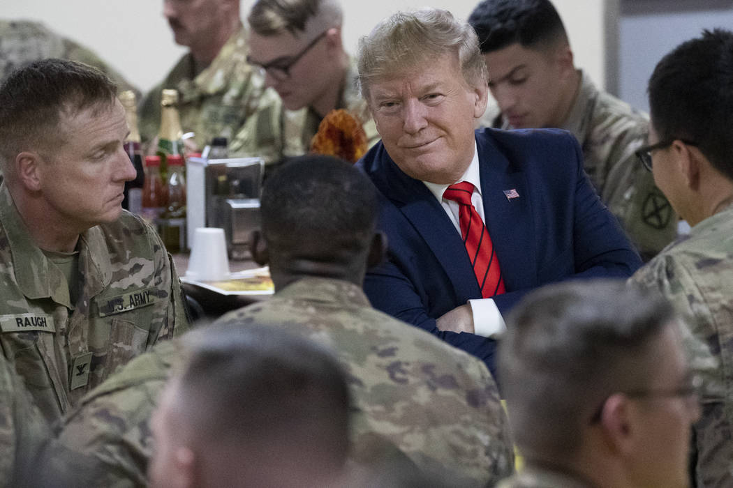 President Donald Trump smiles while sitting with the troops during a surprise Thanksgiving Day ...
