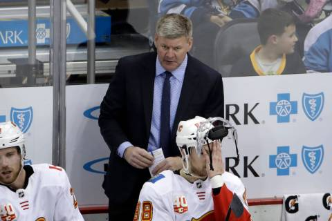 Calgary Flames head coach Bill Peters stands behind Andrew Mangiapane (88) during the third per ...