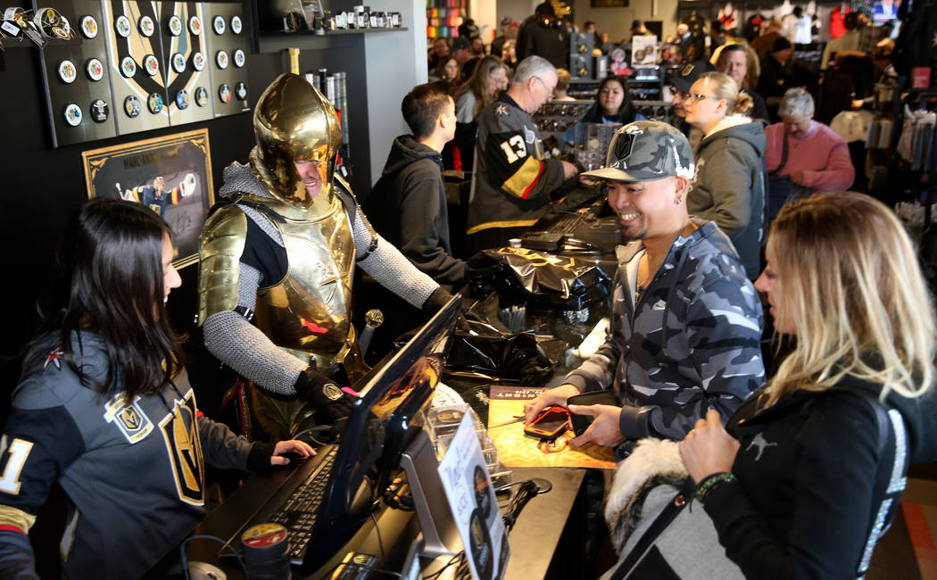The Golden Knight steps in to help Vivika Kim, left, ring up Mike and Stephanie Ibasco of Mount ...