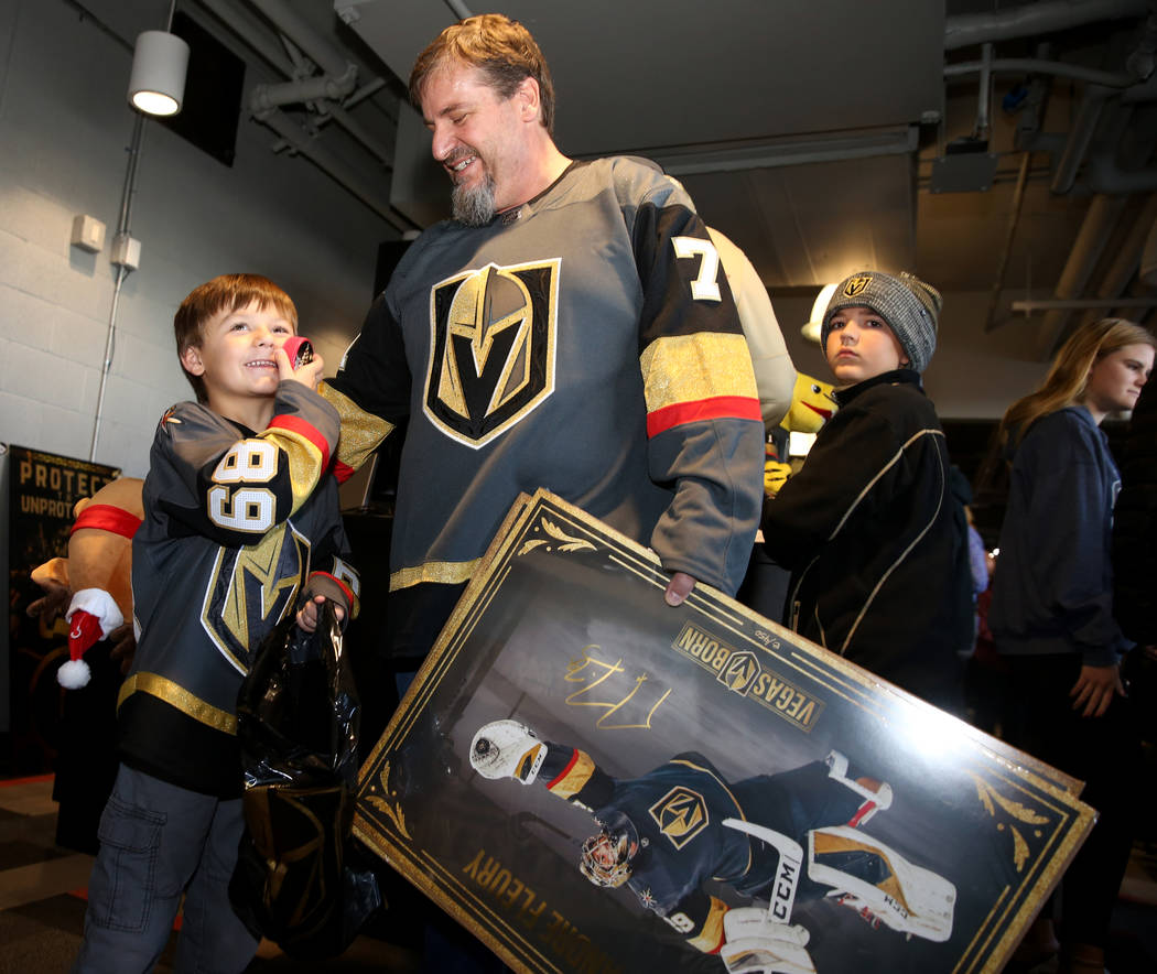 Silus Wells, 5, and his dad Steve Wells of Las Vegas show off their purchases at The Arsenal re ...