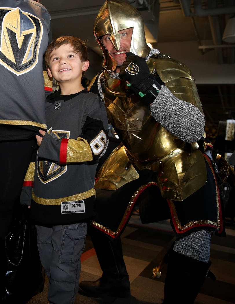 Silus Wells, 5, poses with The Golden Knight at The Arsenal retail store at City National Arena ...