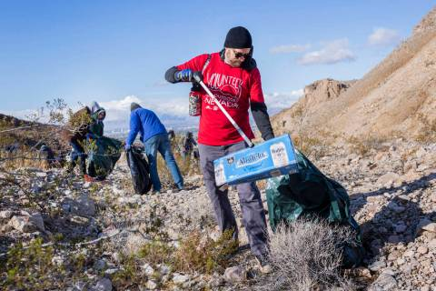Volunteer for Get Outdoors Nevada Chris Moore picks up garbage near the trail leading to the Gr ...