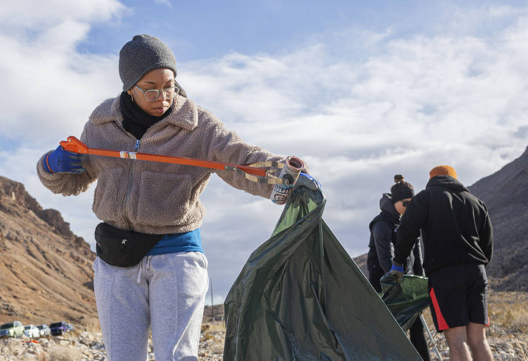 Volunteer for Get Outdoors Nevada Jasmine Upperman of Los Angeles cleans up trash near the trai ...