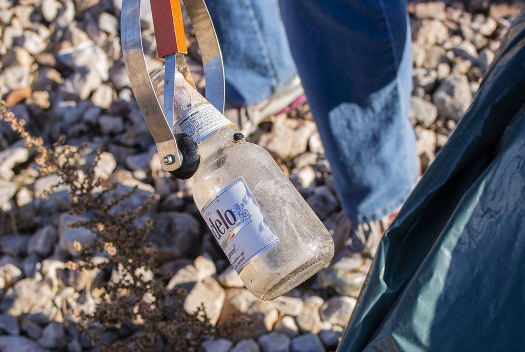 A volunteer for Get Outdoors Nevada picks up a glass beer bottle near the trail leading to the ...