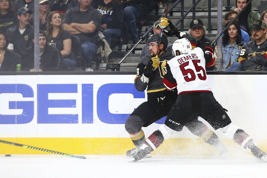 Golden Knights' William Carrier, left, and Arizona Coyotes' Jason Demers (55) battle to reach t ...