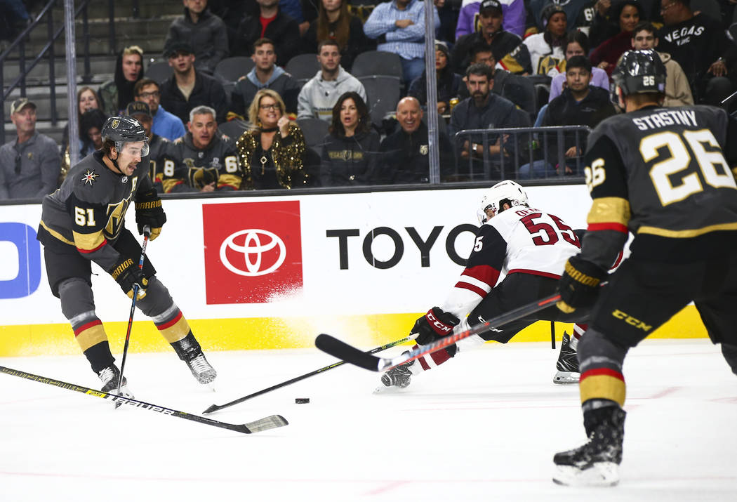 Golden Knights' Mark Stone (61) sends the puck past Arizona Coyotes' Jason Demers (55) during t ...