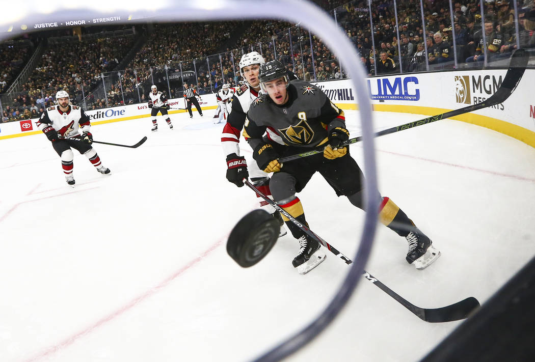 Golden Knights' Reilly Smith (19) and Arizona Coyotes' Jakob Chychrun (6) watch the puck fly to ...