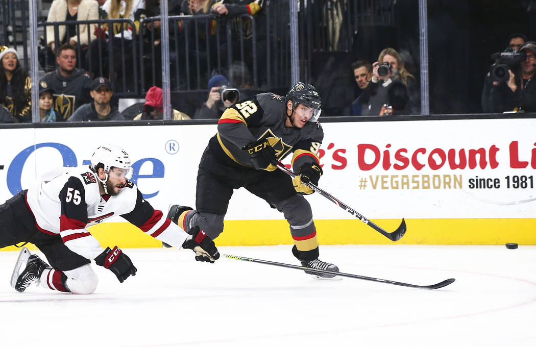 Golden Knights' Tomas Nosek (92) shoots the puck in front of Arizona Coyotes' Jason Demers (55) ...