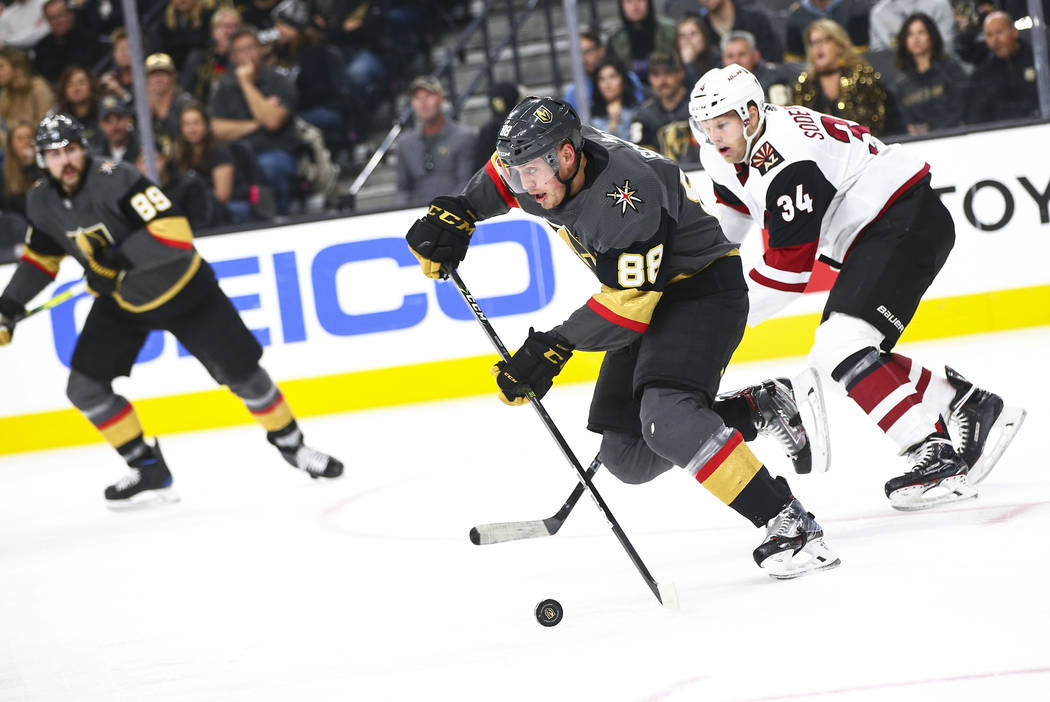 Golden Knights' Nate Schmidt (88) skates with the puck in front of Arizona Coyotes' Carl Soderb ...