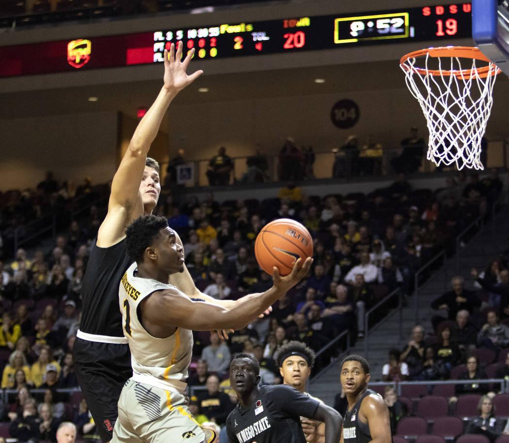 University of Iowa's Joe Toussaint (1) jumps to dunk the ball as SDSU's forward Yanni Wetzell, ...