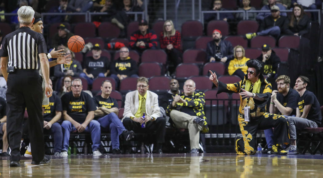 University of Iowa fan Greg Suckow, dressed as Elvis, tosses the ball back into play during the ...