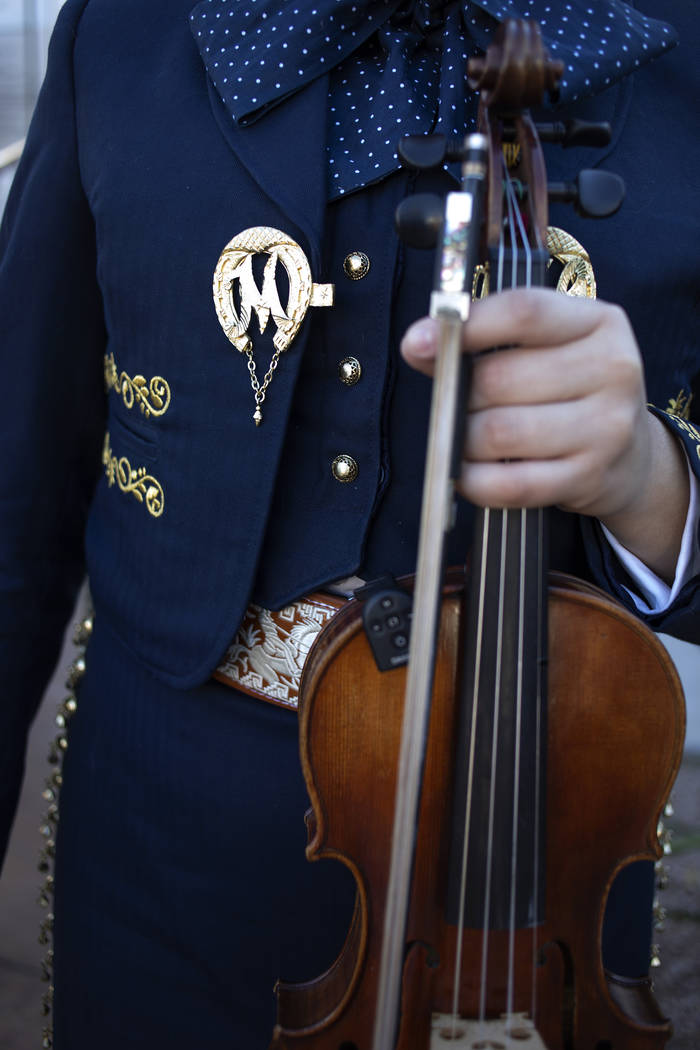 A member of Mariachi Herencia pauses before performing in her traditional mariachi garb at the ...