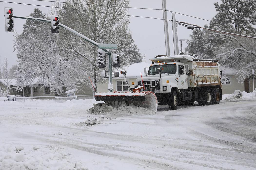 A city snowplow helps clear roads north of downtown Flagstaff, Ariz., Friday, Nov. 29, 2019. A ...