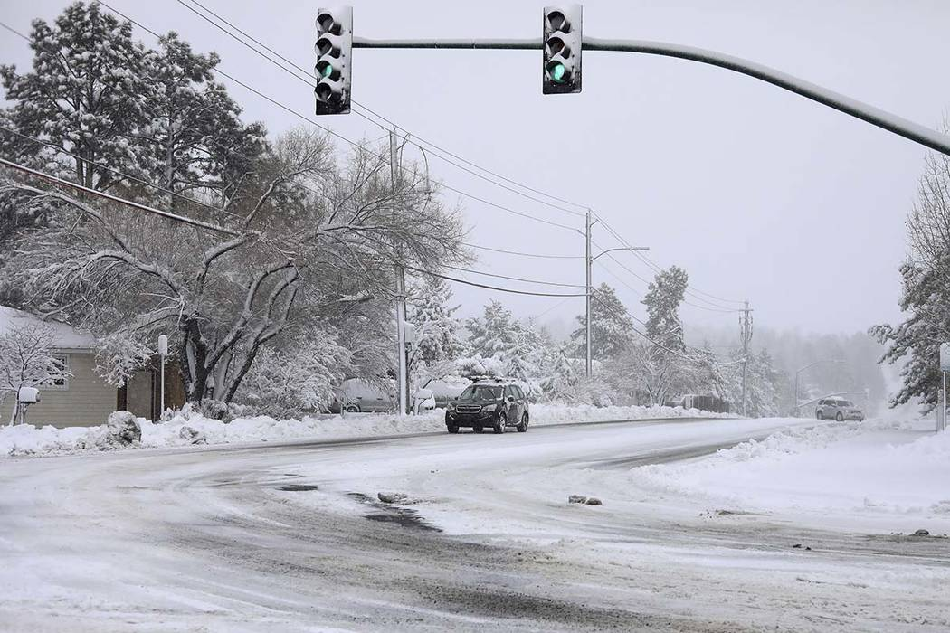 Commuters drive as the snow continues to fall north of downtown Flagstaff, Ariz., Friday, Nov. ...