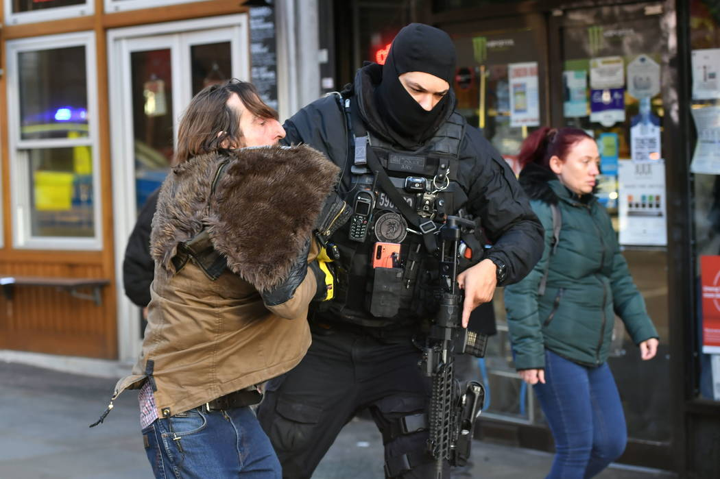 A police officer moves an uninvolved person away from a cordon after an incident on London Brid ...